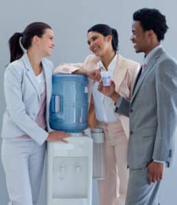Three employees gathered around the water cooler